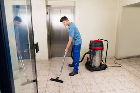 Happy Male Worker Cleaning Floor With Vacuum Cleaner Appliance Foto de archivo