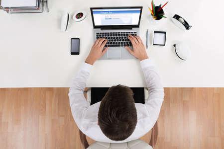 노트북을 사용하는 온라인 계정에 로그인을하는 사업가의 높은 각도보기
