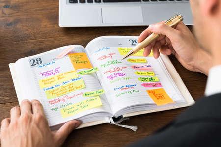 Close-up Van Businessperson leeslijst van het werk in Diary