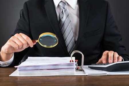 Close-up Of Businessman Inspecting Invoice With Magnifying Glass At Wooden Desk