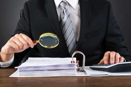 Close-up Van Zakenman Inspecteren Invoice Met Vergrootglas Op Wooden Desk Stockfoto