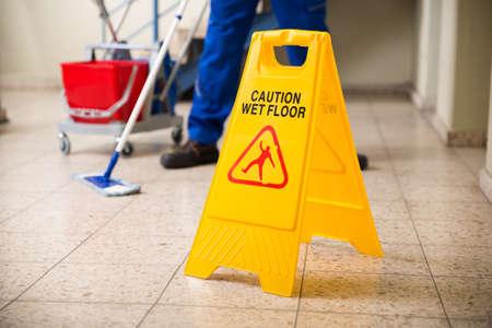 Low Abschnitt Worker Mopping Fu�boden Mit Wet Floor Achtung-Zeichen auf Fu�boden