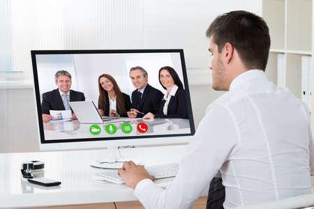 Businessman Videoconferencing With Co-workers On Desktop Computer At Desk