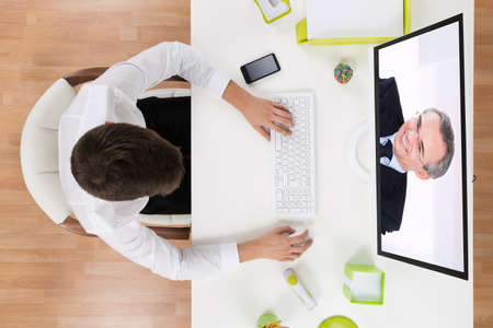 business conference: Young Businessman Videochatting With Senior Staff On Computer In Office