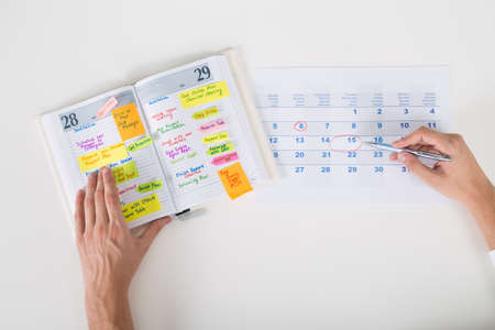 Close-up Of Person Hands Highlighting Date On Calendar With Diary At Desk 免版税图像
