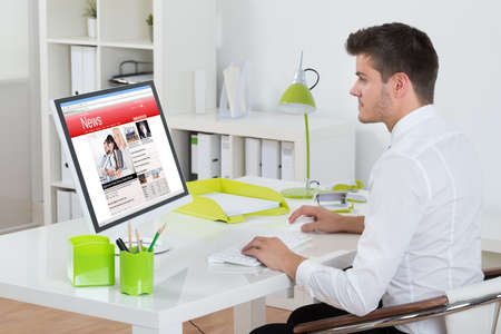 viewing: Young Businessman Watching Online News On Computer At Workplace