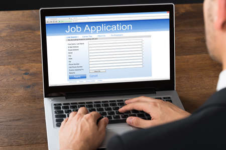 trabajo: Primer plano del hombre de negocios de llenado del trabajo en línea formulario de solicitud en la computadora portátil