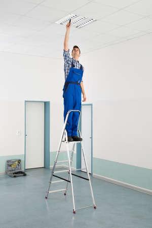 天井のライトをインストールする脚立男性電気工事 写真素材