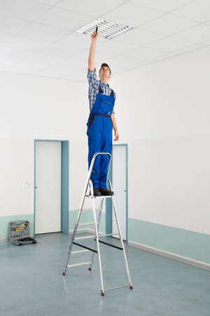 office ceiling: Male Electrician On Stepladder Installing Ceiling Light Stock Photo