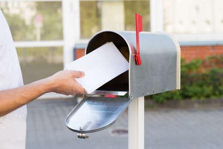メールボックスのスタック文字を置く人のクローズ アップ 写真素材