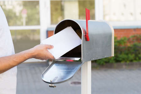 metal post: Close-up Of Person Putting Stack Of Letters In Mailbox