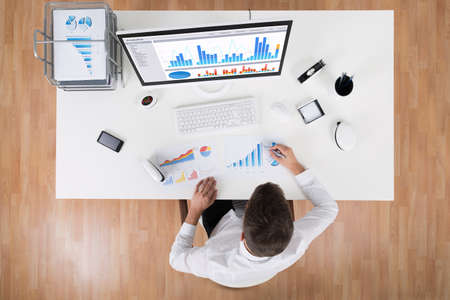 plan view: High Angle View Of Businessman Analyzing Statistical Graphs At Desk Stock Photo