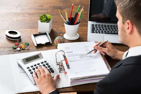contadores: Primer plano del hombre de negocios Cálculo Recibo Con la calculadora en el escritorio