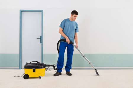 carpet: Young Male Cleaner In Uniform Vacuuming Floor