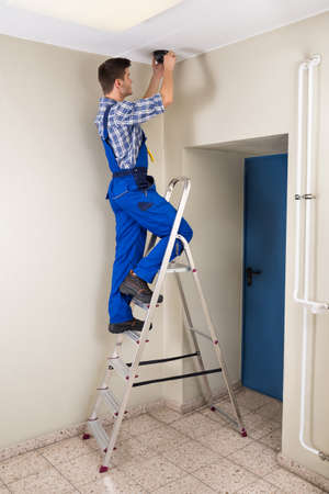 stepladder: Male Technician Standing On Stepladder Fitting Cctv Camera