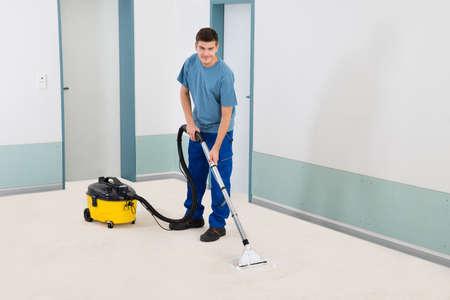 personal de limpieza: Limpiador Hombre Joven En Uniforme aspiradora piso