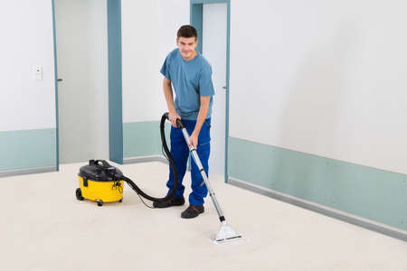 vacuum: Young Male Cleaner In Uniform Vacuuming Floor