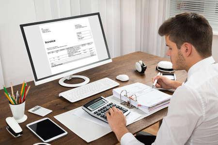 contabilidad financiera cuentas: Hombre Contable Cálculo de Impuestos delante del ordenador en el escritorio Foto de archivo