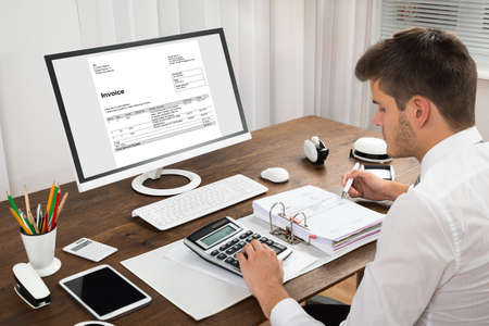 INVOICE: Male Accountant Calculating Tax In Front Of Computer At Desk
