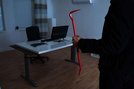 noiseless: Close-up Of Burglar Holding Crowbar In Office