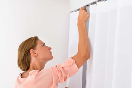 white curtain: Young Woman Putting White Curtain At Home