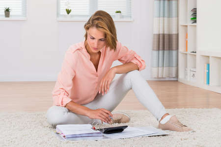 invoices: Young Woman Sitting On Carpet Calculating Invoices With Calculator