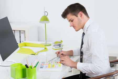 gantt: Young Businessman Working On Gantt Chart In Front Of Computer At Desk Stock Photo