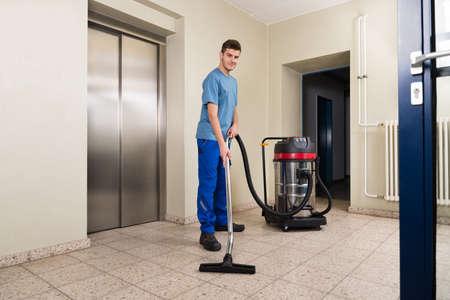 진공 청소기 어플라이언스와 함께 행복 한 남성 노동자 청소 층