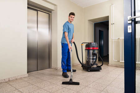 office appliances: Happy Male Worker Cleaning Floor With Vacuum Cleaner Appliance Stock Photo