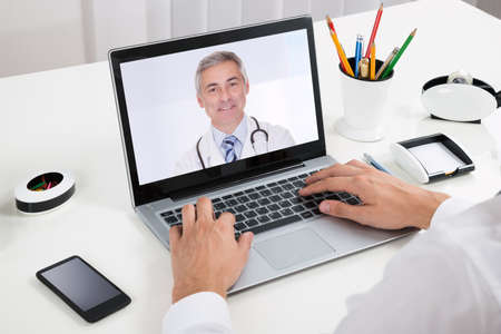 doctor laptop: Close-up Of Businessperson Videochatting With Doctor On Laptop At Desk Stock Photo