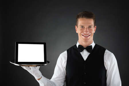 blank tablet: Young Butler Holding Tray With Blank Display Digital Tablet