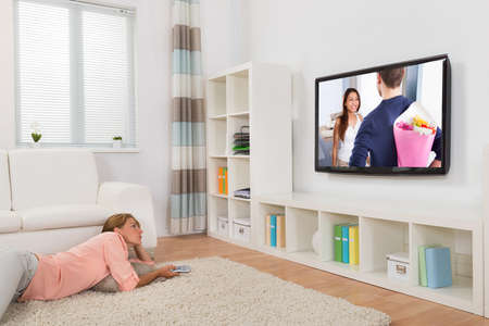 home cinema: Young Woman Watching Movie While Lying On Carpet In Living Room