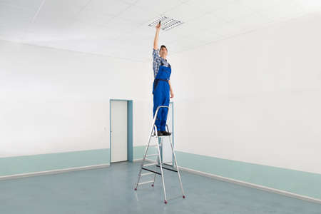 ceiling: Male Electrician On Stepladder Installing Ceiling Light Stock Photo