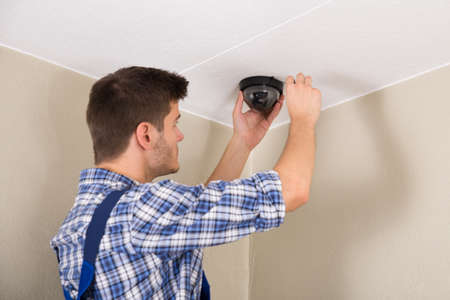 man with camera: Young Male Technician Installing Surveillance Camera On Ceiling