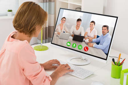 コンピューター デスクで同僚と若い女性会議