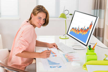 analyzing: Young Happy Woman Analyzing Financial Statistics In Office