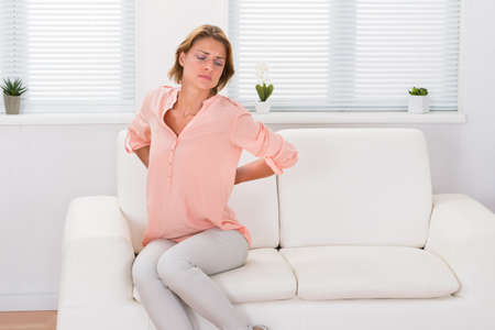 sit: Young Woman Sitting On Sofa Suffering From Backache Stock Photo