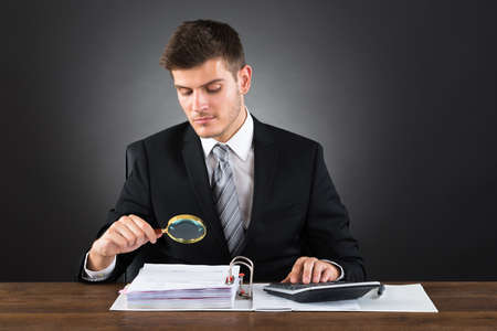 fraud: Young Businessman Scrutinizing Invoice With Magnifying Glass