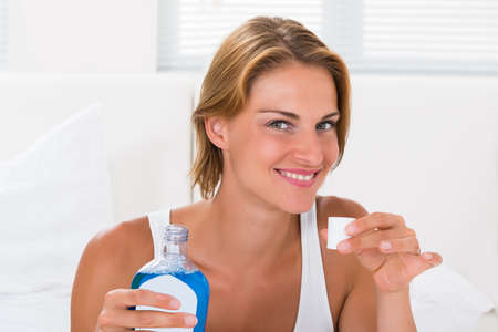 enjuague bucal: Hermosa Mujer Feliz sosteniendo la botella de enjuague bucal