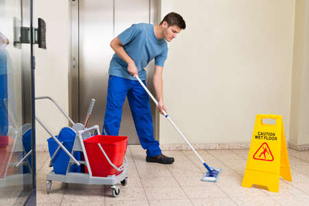 cleaning an office: Happy Male Janitor With Cleaning Equipments Mopping Floor