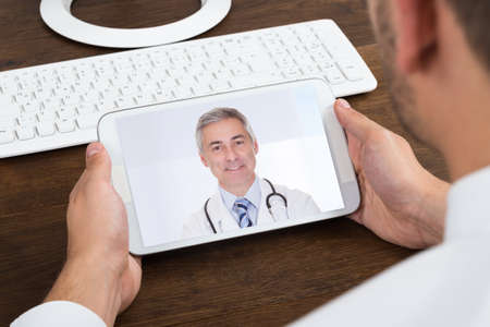 business phone: Close-up Of Businessperson Videochatting With Senior Doctor On Mobile Phone Stock Photo