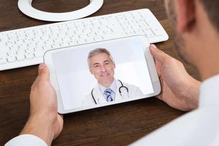 person calling: Primer De Empresario Videochatting Con Doctor mayor en el tel�fono m�vil
