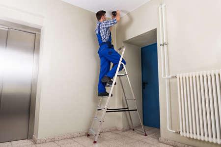 setup man: Male Technician Standing On Stepladder Fitting Cctv Camera