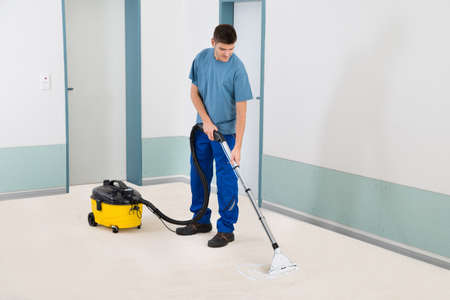 dirty carpet: Young Male Cleaner In Uniform Vacuuming Floor
