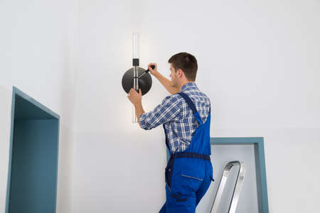 Male Electrician Standing On Stepladder Repairing Light 스톡 콘텐츠