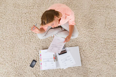 folder with documents: High Angle View Of Young Woman Doing Calculation At Home