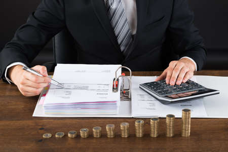 Close-up Of Businessman Calculating Invoice With Coins At Desk Imagens - 45705774