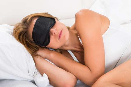 dormir: Mujer joven que duerme con la máscara del sueño en la cama