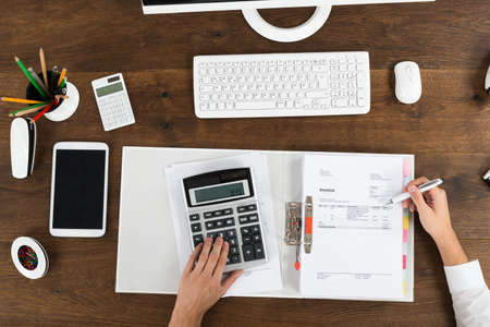contabilidad financiera: Vista elevada de Empresario del impuesto Cálculo en el escritorio de madera Foto de archivo