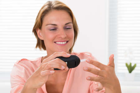 Close-up Of Young Happy Woman Checking Glucose Level With Glucometer